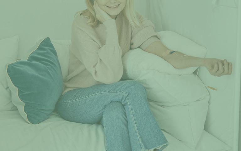kobieta siedząca nakanapie przyjmująca suplementy dożylnie