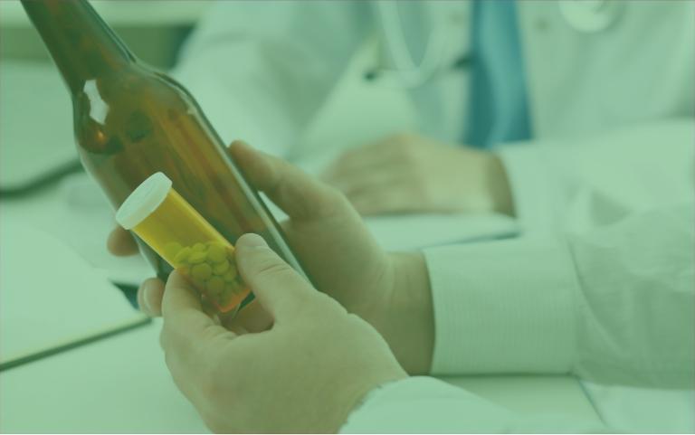 Pacjent trzymający butelkę poalkoholu itabletki