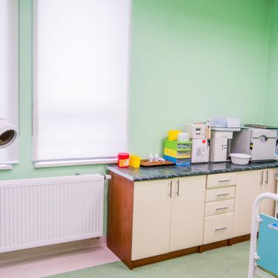 Gabinet z zielonymi ścianami i łóżkiem