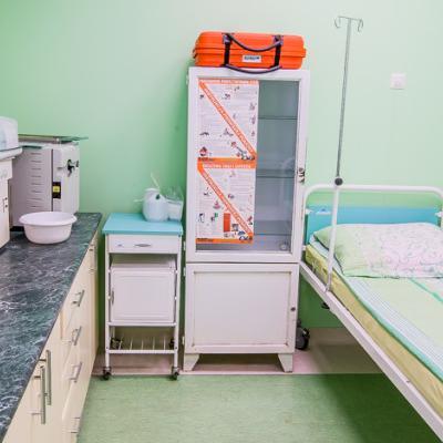 Gabinet z zielonymi ścianami szafką i łóżkiem